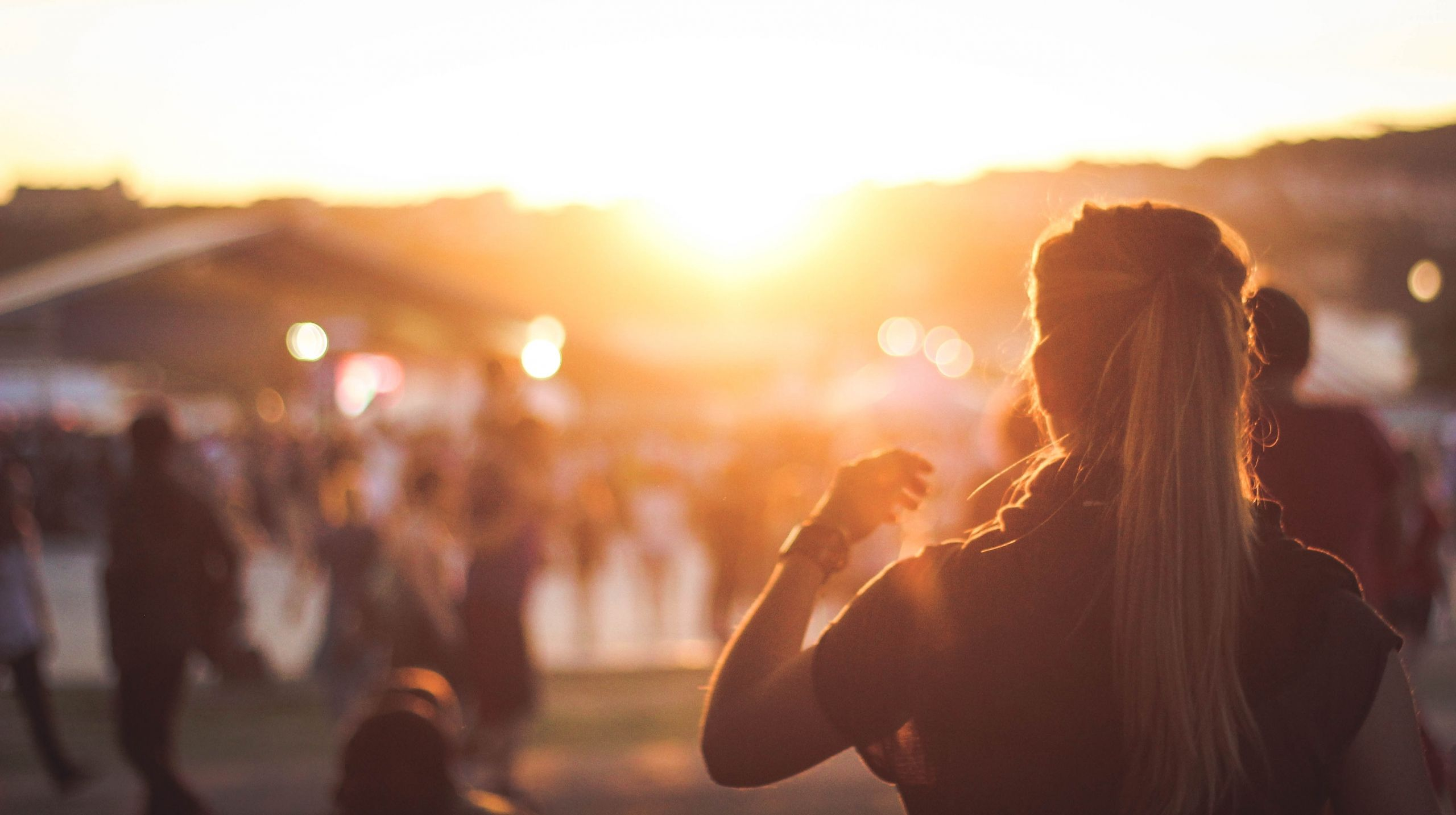 Person Enjoying Music Event with Sunset in background